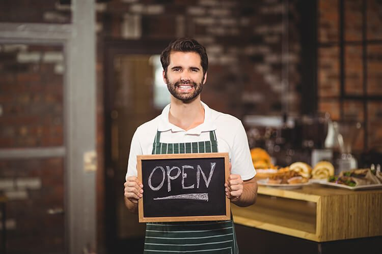 Smiling waiter showing chalkboard with open sign encouraging shopping local.