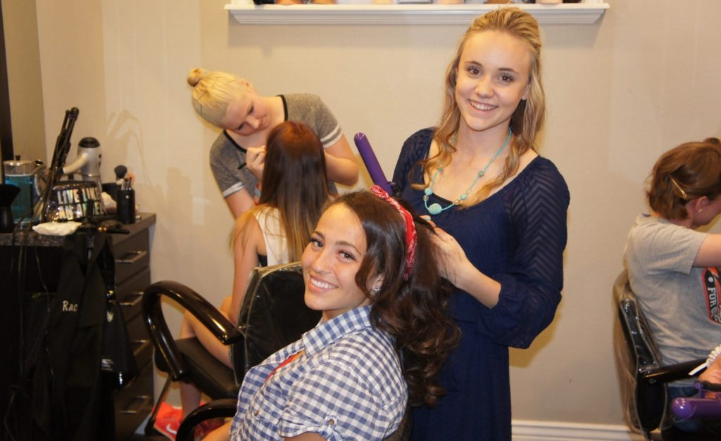 Loyal customer and hairstylist curling and fixing hair at The Forum Academy.